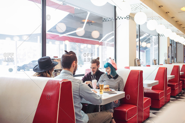 Two young couples eating vegetarian burgers at retro fast food restaurant