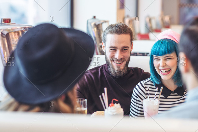 Group of men and women sitting at diner restaurant and smiling