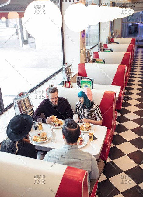 Couples eating vegetarian burgers and french fries at diner restaurant