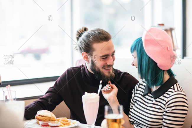 Young stylish man and woman in love eating vegetarian burgers an milkshake at vintage diner restaurant