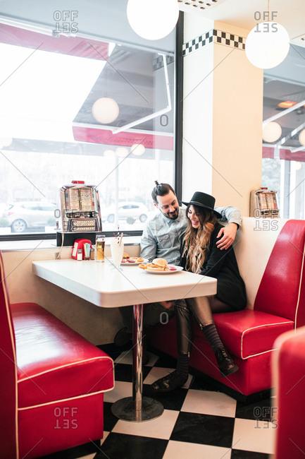 Stylish couple cuddling at vintage fast food restaurant