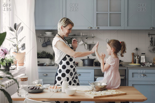 Mother and her little cute daughter playing smiling and having fun at kitchen at home