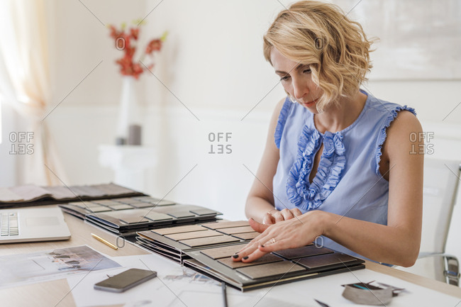Pretty Caucasian woman interior designer working with material palette at her office