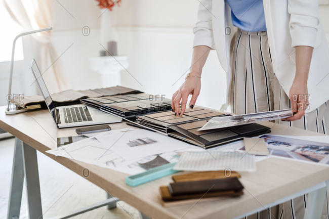 Hands of unrecognizable woman interior designer working with material palette at her office