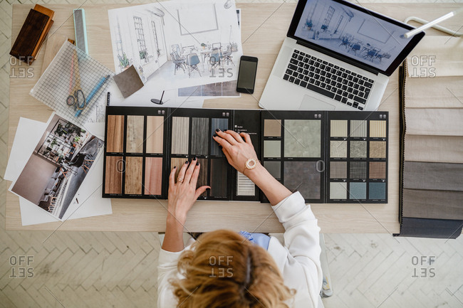 Overhead photo of woman interior designer working with material palette at her office