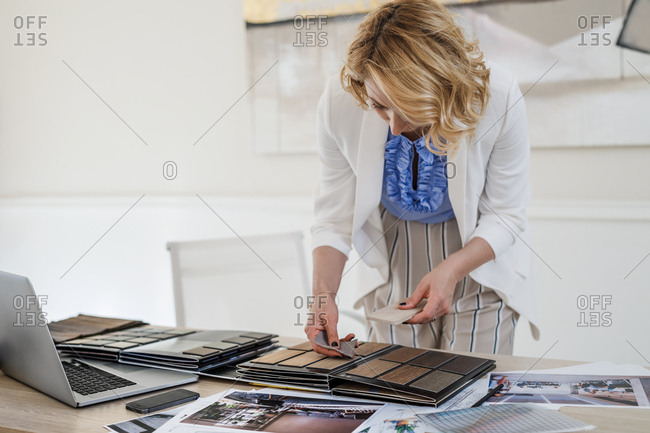 Pretty Caucasian woman furniture designer working with material palette at her atelier