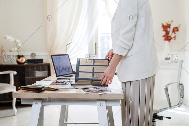 Hands of unrecognizable woman furniture designer working with material palette at her office