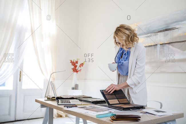 Elegant businesswoman interior designer working standing at her office an looking at wood palette
