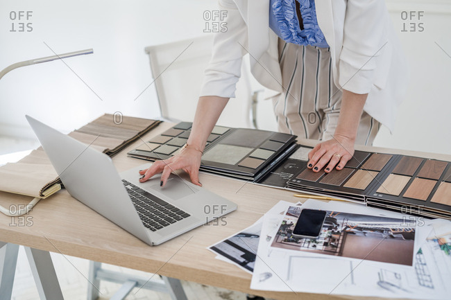 Hands of unrecognizable woman interior designer working with material palette and typing on her laptop