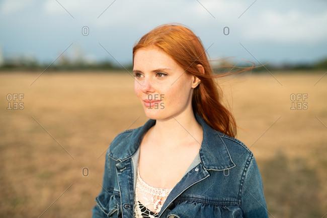 Young redhead teenage girl wearing jean jacket looking away