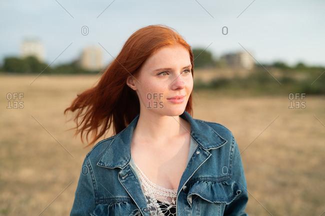 Red haired teenage girl wearing jean jacket looking away
