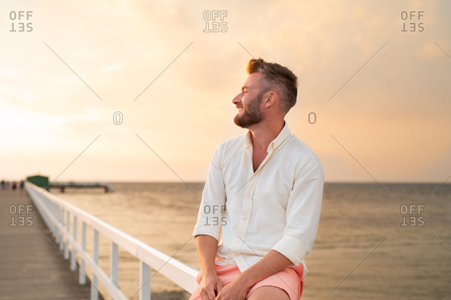 Happy man with facial hair sitting on boardwalk at sunset