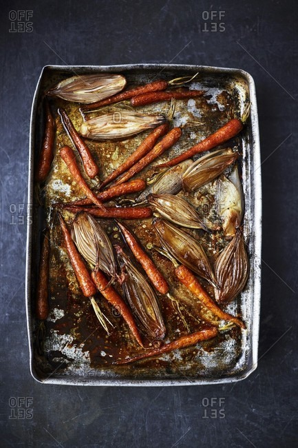 Roasted carrots and shallots on a baking tray