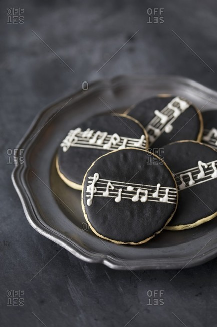 Round cookies with black icing and a stave and notes pattern