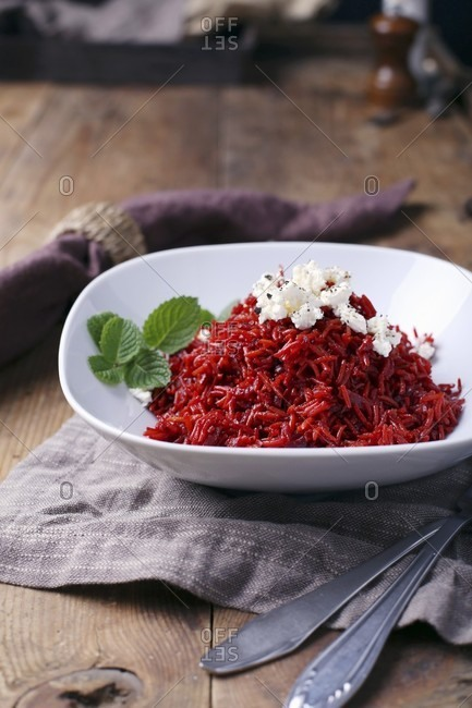 Beetroot risotto with feta cheese and mint in a white bowl on a wooden table