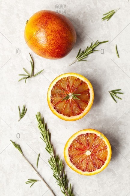 Blood oranges, whole and halved, with rosemary