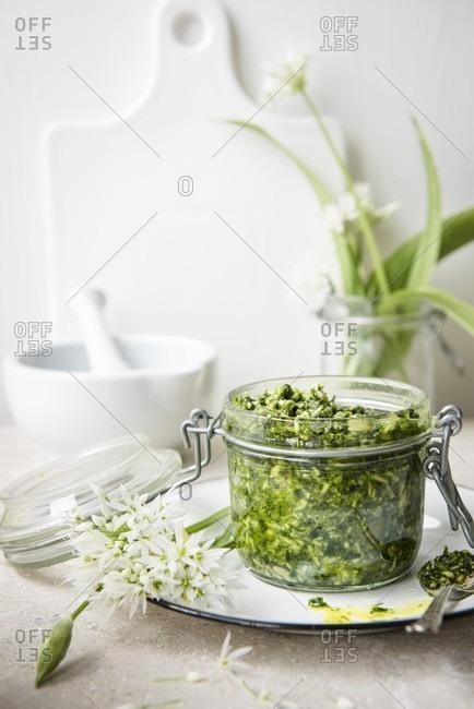 A jar of wild garlic pesto and fresh wild garlic with flowers