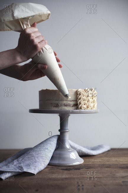 A cream cake being decorated with peanut butter cream