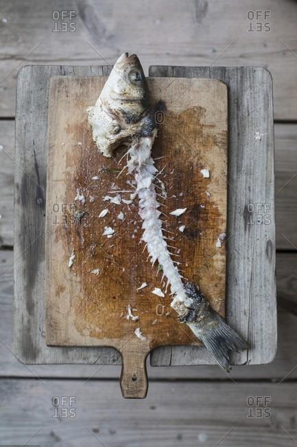 A branzini carcass on a chopping board