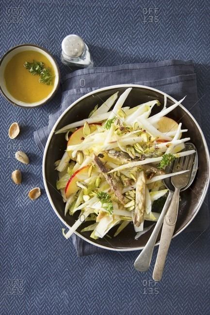 Chicory salad with apple, pistachios and fish fillets