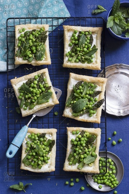 Puff pastry tartlets topped with asparagus, green peas, mint, goat's cheese and lemon zest