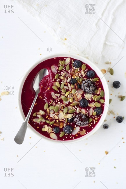 A berry smoothie bowl with pumpkin seeds, sesame seeds and almonds