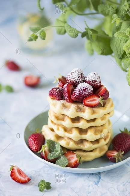Fresh waffles with strawberries and icing sugar