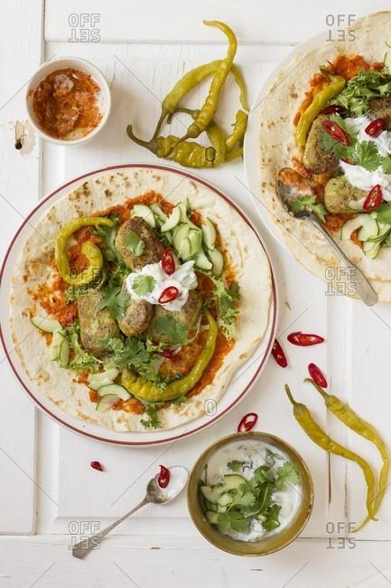 Vegetarian kofta with harissa, yoghurt, cucumber, coriander and hot green peppers on a tortilla