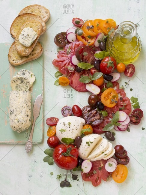 Tomato and mozzarella salad with radishes, herbs, olive oil, garlic and herb butter and bread