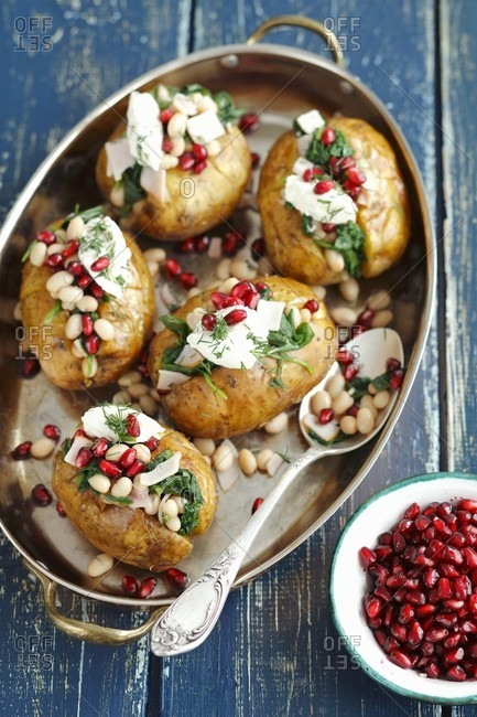 Baked potatoes stuffed with spinach, ham and bean salad and topped with cream cheese and pomegranate seeds