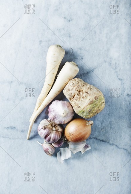 Celery, parsley, garlic and onion on a marble background