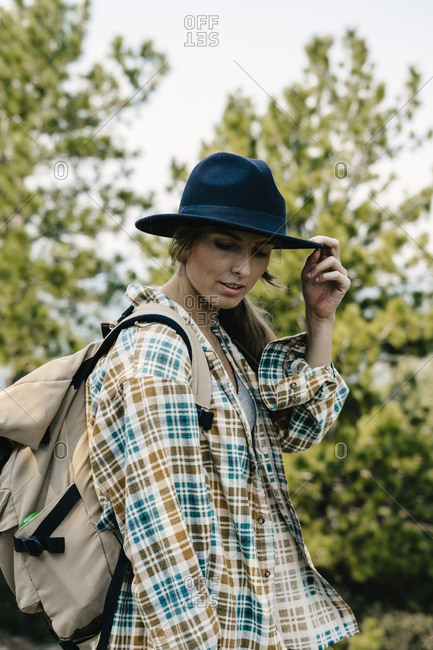 Young woman wearing backpack tipping her hat