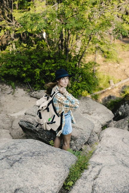 Young woman wearing backpack looking over shoulder while hiking on a trail through boulders