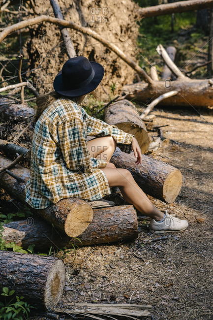 Young woman sitting on a log looking up into the forest