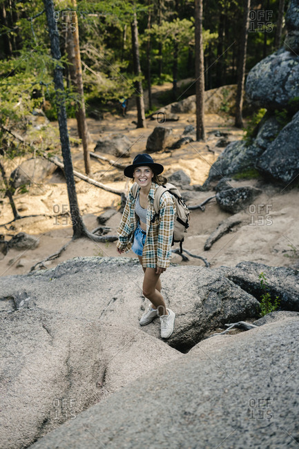Happy woman backpacking on mountain in the Stolby Nature Sanctuary