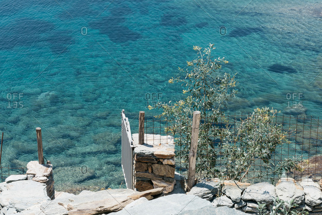 Open gate along rugged beach with clear blue water
