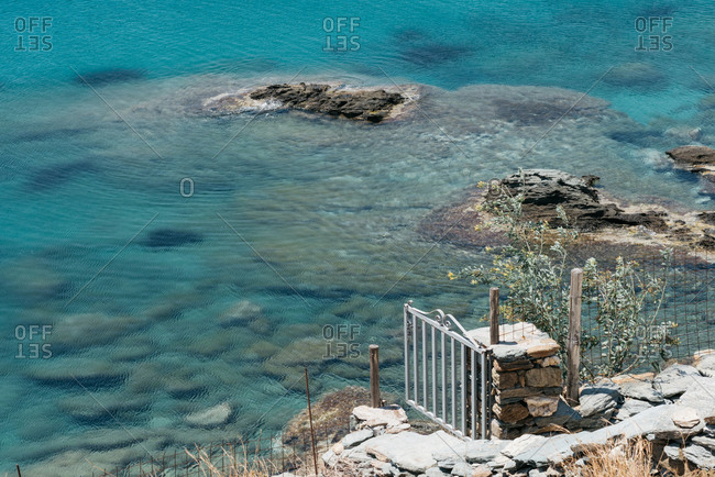 Open gate leading to rugged beach with clear water