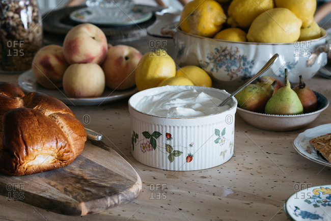 Fresh Greek yogurt served with loaf of bread and fruits