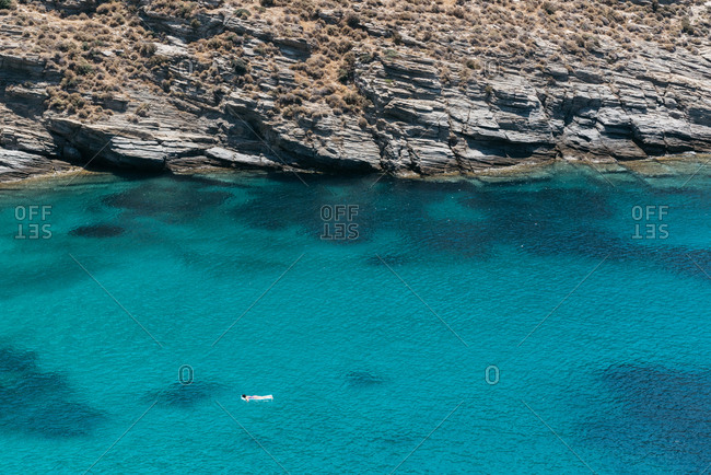 Person floating in blue water off the rocky coast on the island of Andros