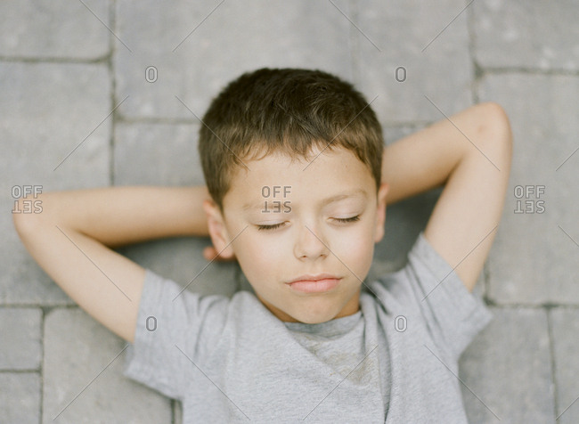 Boy lying on ground with hands behind head and eyes closed