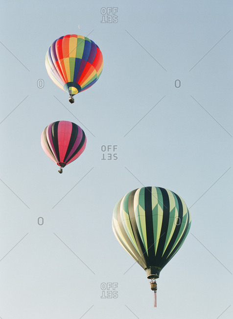 Three colorful hot air balloons against clear sky