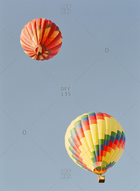 Two brightly colored hot air balloons from below