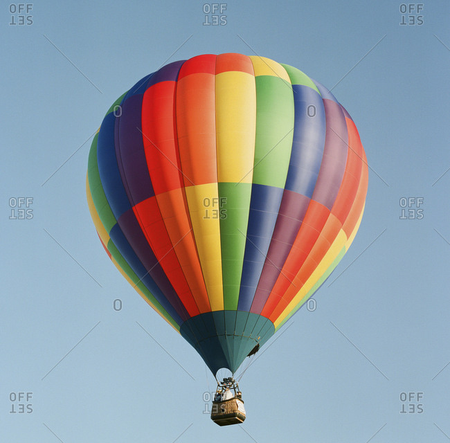 Solitary brightly colored hot air balloon against clear sky