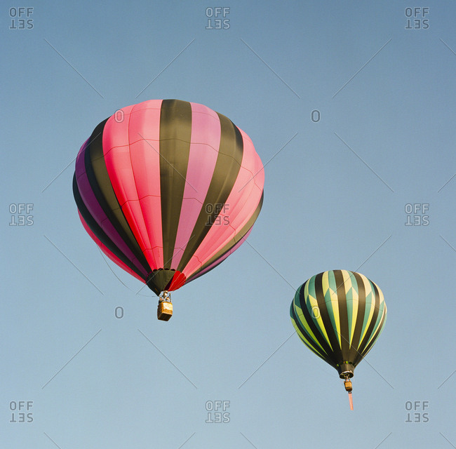 Two brightly colored hot air balloons against clear sky