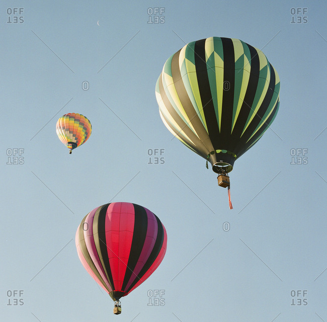Three colorful hot air balloons from below
