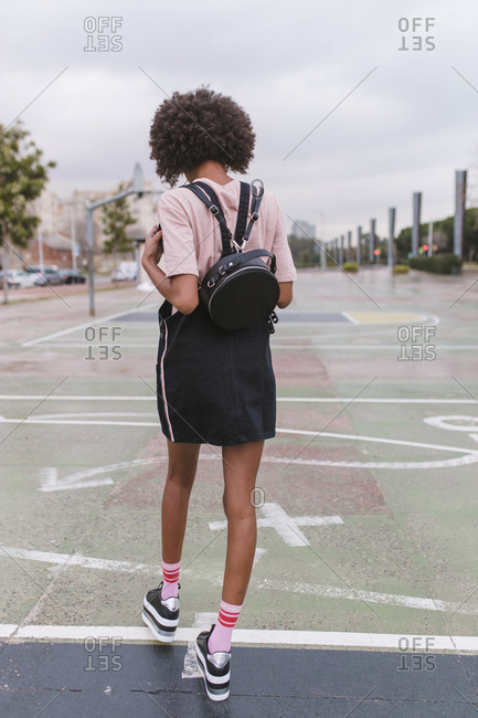 Young african-american girl walks by the basketball court