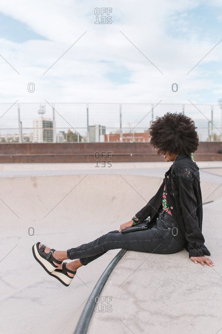 African-american young girl sitting on a skate park ramp in a cloudy day palms background