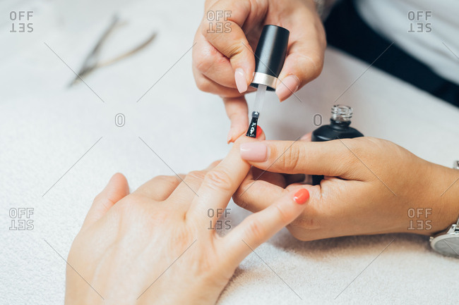 Close up beautician applying nail varnish on customer - health and beauty, manicurist, glamour concept