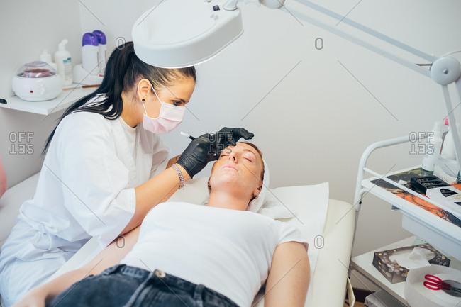 Beautician removing facial hair on a customer - spa treatment, facial hair, epilation concept