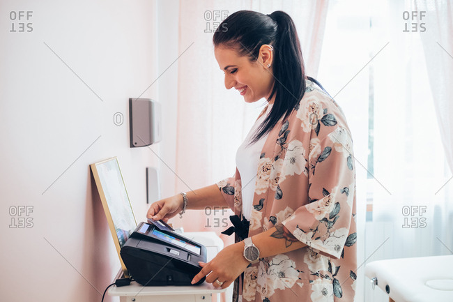 Young adult woman doing payment on a credit card reader - buying, paying, customer concept